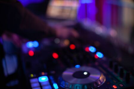 Dj mixing music in night club, defocused bokeh music light for background. Music dance party time in night club
