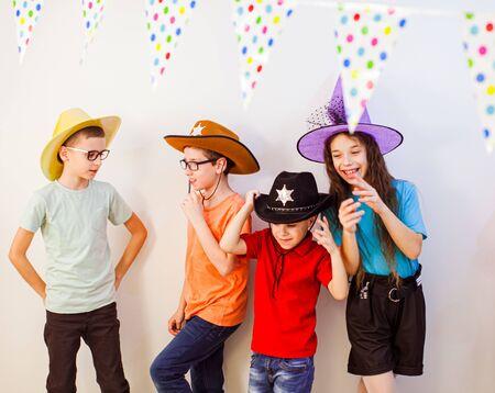 Grupo de niños celebran la fiesta de cumpleaños. Amigos en traje festivo y sombreros divirtiéndose juntos