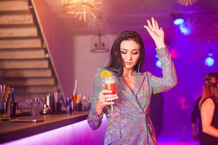 Luxury fashionable woman drinks alcohol cocktail and dancing in club