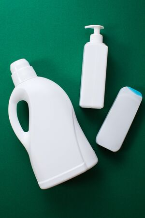 Plastic bottles of cleaning products over green background. Top view. Flat lay. Copy space. Plastic waste.