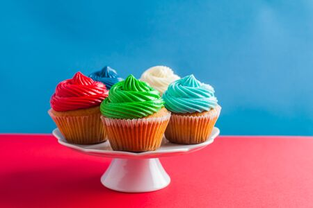 Five delicious cupcakes with colorful icing standing on a white cakestand, isolated on two-colored red and blue background