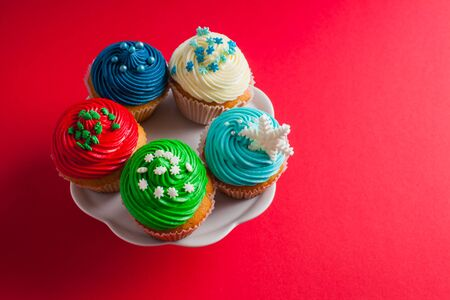 Top view of five muffins covered with multicolored buttercream topping, standing on a white plate. Isolated on a pink red background 免版税图像 - 139602618