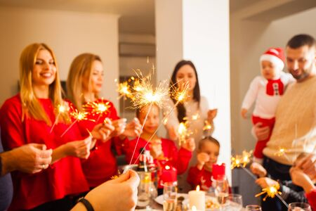 Close up photo of womans hand holding lighted sparkles, group of happy smiling men and women with kids on a background, holding sparkles, blured. Christmas celebration Standard-Bild - 139602544