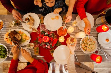 Flat-lay photo of table for traditional Christmas, New Year holiday celebration party. Friends or family feasting with turkey or chicken, vegetables, wine, top view Standard-Bild - 139602477