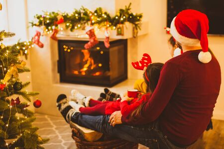 Back side view of young father in Santa Clause hat sitting with his legs on a basket with wood, holding his daughter. Cute girl in red dress drinking tea, sitting with his father near fireplace