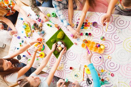 Top view of kids hands holding Easter crafts and colored eggs. Group of children working together creating Easter decorations Standard-Bild - 139603053