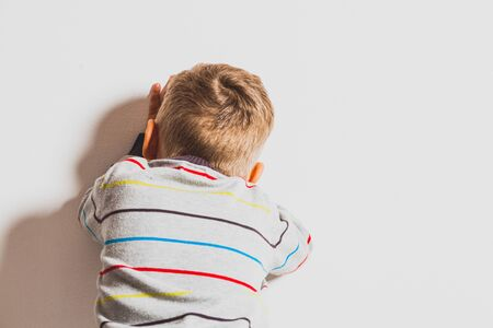 Frustrated little 2 years boy crying near the white wall. Emotional conflict Stock Photo