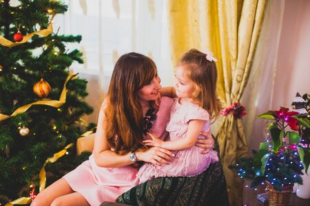 Cheerful mom and her cute daughter girl having fun near Christmas tree at home Foto de archivo - 139719684
