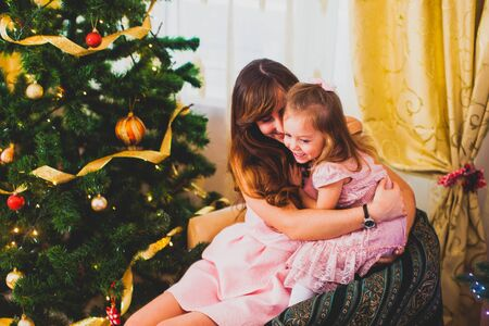 Young mother and daughter make a wish at Christmas night Foto de archivo - 139719679
