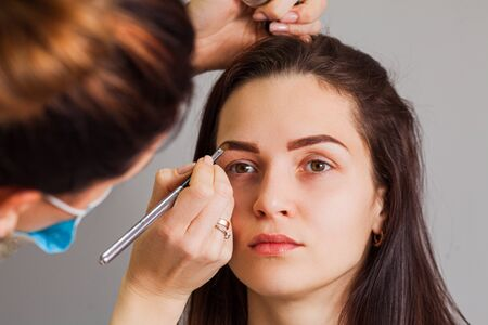 Young woman having professional eyebrow correction procedure Imagens