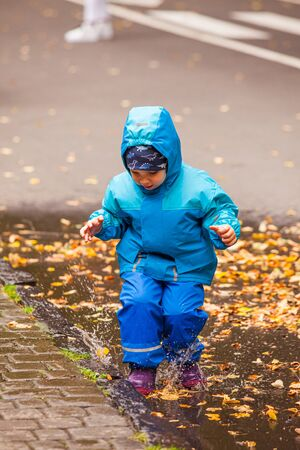 The small boy in blue clothes is jumping in a puddle with yellow leaves lifting splashes