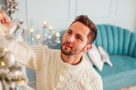 Top view of young man decorating Christmas tree Stock Photo