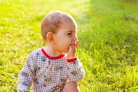 Baby with chicken pox rash sitting at green grass
