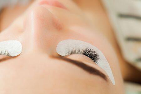 Beauty model with perfect fresh skin and long eyelashes. Skincare, eyelash extension procedure.