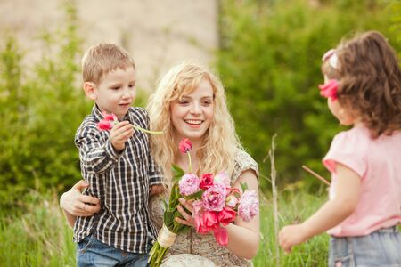 Little daughter and son congratulates mother and giving her flowers bouquet in spring garden