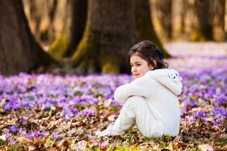 Little girl in white warm romper outdoors in spring forest