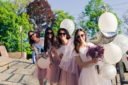 Girls wearing on pink dresses having fun on hen party.