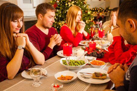 Freunde, die vor dem Essen konzentriert auf ihr Gebet sitzen
