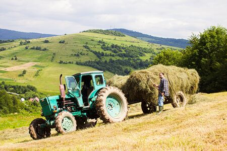 The tractor harvesting hay in the field on the background of a incredibly beautiful landscape