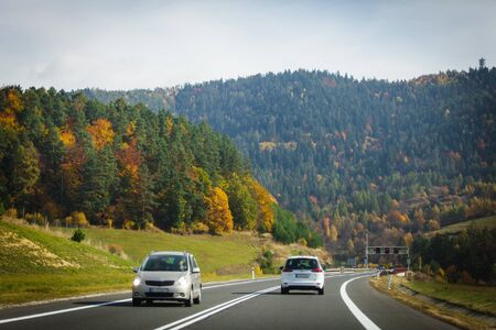 Cars driving on the asphalt road passing through the mountain pass. The concept of traveling to the mountains at the autumn