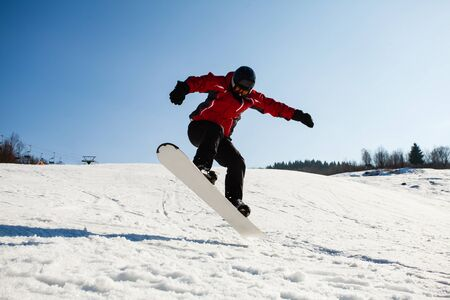 Skilled snowboarder jumping over snow slope. Sunny winter day, hill covered with snow, male snowboarder in action.