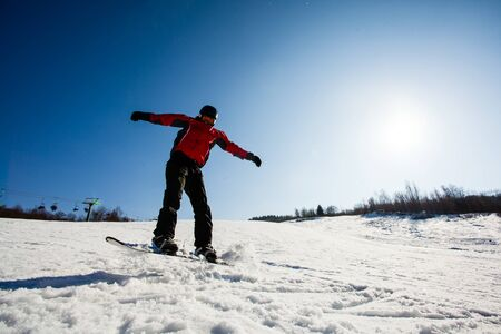 Action photo of professional snowboarder riding down the hill on sunny frosty day.