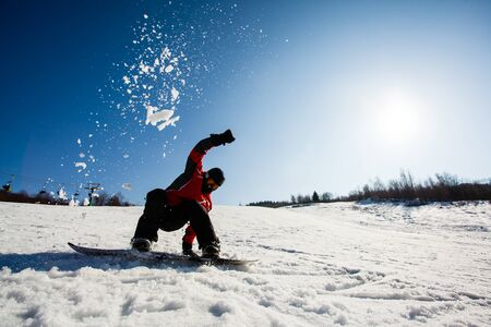 Male snowboarder in the momemt of falling down on the snow. Cloud of snow over his head. Blue sky with bright sun on a background
