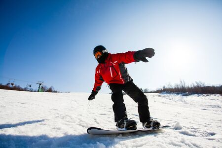 Close portrait of young snowboarder freeriding the snow slope on a sunny winter day. Blue sky on a background