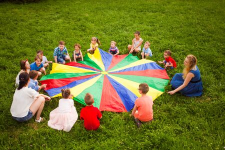 Big group of children playing parachute game on the green field