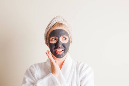 Young beautiful woman in a mask for the face of the therapeutic black mud