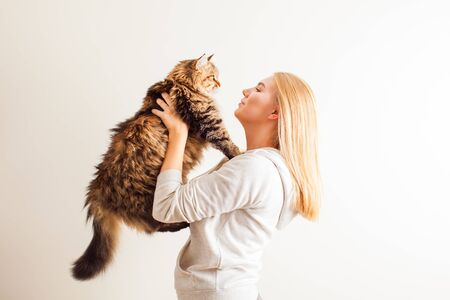 Young woman holding new adopted siberian cat
