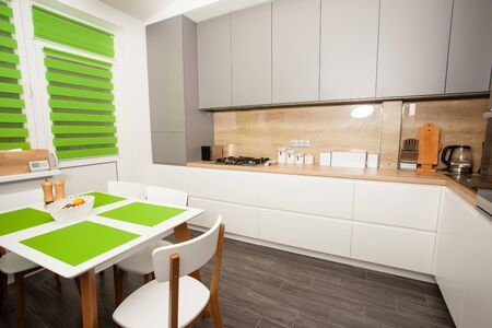 Moden white and greuy interior with green accessories for kitchen. Kitchen eating table and simplistic accents.