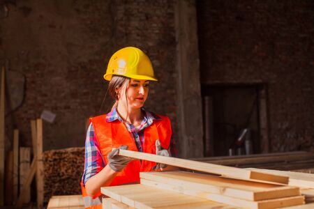 Woman worker sorting wood at production factory. Gender equality concept.