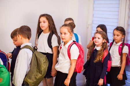 School children in uniform with backpacks going to class