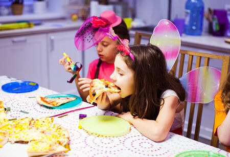 Cute little girl eats pizza at party. Pretty girl in butterfly costume. Birthday party