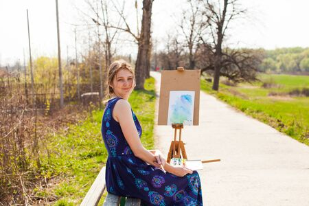 Student girl artist painting landscape in the open air in early spring.