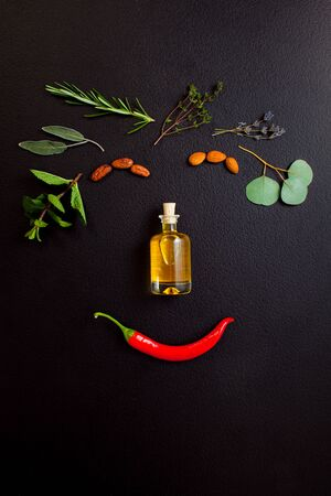Smiling face making from herbs and bottle of essential oil on black background, top view, flat lay. Healthy organic handmade cosmetics