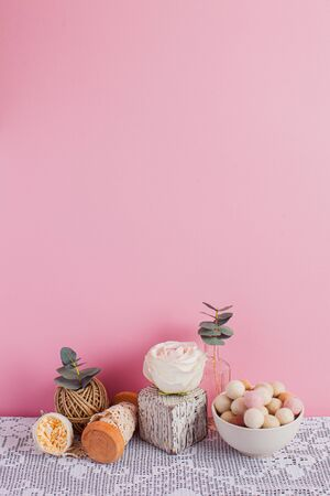 Vertical still life on pink background. Bowl with felt bals, white cube with rose on top, skein of braid, crocheted table cloth. Copy space