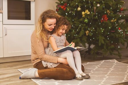 Story time with mother and daughter near Christmas tree Reklamní fotografie