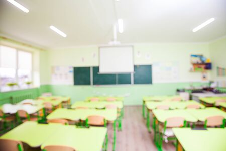 Wide angle large light schoolroom with yellow desks placed in strict rows. Chalkboard and whiteboard. Picture defocused, background for design