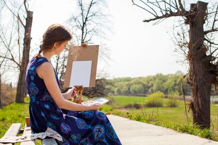 Young female artist painting picture in spring park. Pretty girl sitting on bench and drawing landscape. Foto de archivo - 141068473