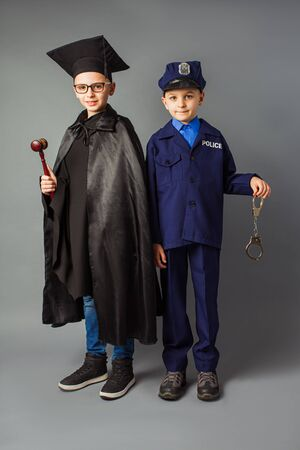 Kids and future education concept. Two kids wearing costume of policeman and judge.