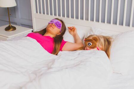 Mom and daughter sleep together with funny sleep masks Foto de archivo