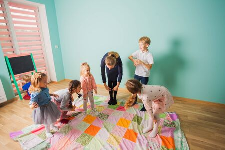 English club for kids. Kids copy the teacher and touch their knees. Active leisure for small children at class. Standard-Bild