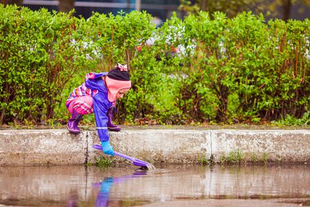 Girl playing in the puddle with plastic shovel