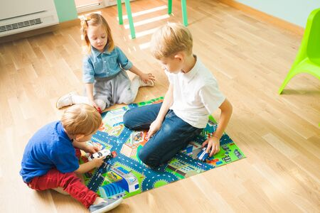 Children playing with cars on a road themed carpet. Kids at home or daycare. Stock Photo