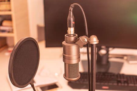 The professional condenser microphone with computer equipment on a blurred background