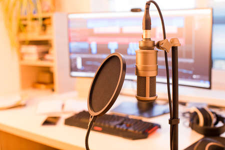 The professional condenser microphone with computer on blurred background in studio with warm light 版權商用圖片