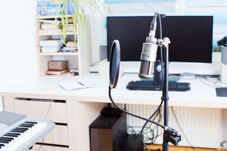 The professional condenser microphone on the background of various equipment for recording and processing music
