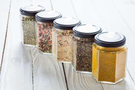 Five glass jars with spice mixtures and dried herbs on white wooden surface. Selection of spices for novice cook